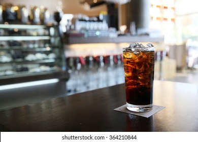 Cola on wood with restaurant background