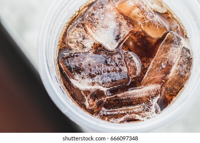 Cola put ice in plastic glass, back ground, blurred.