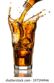 Cola splash in a glass with ice cubes