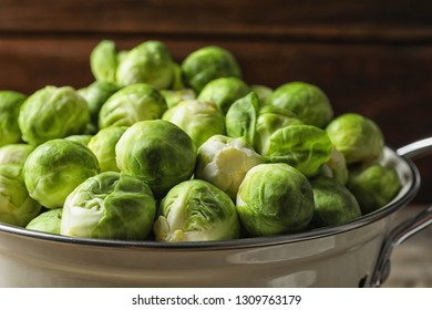 Colander with fresh Brussels sprouts on blurred background, closeup