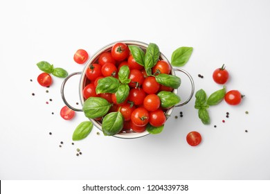 Colander with fresh green basil leaves and cherry tomatoes on white background, top view