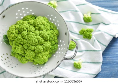 Colander with green cauliflower on table