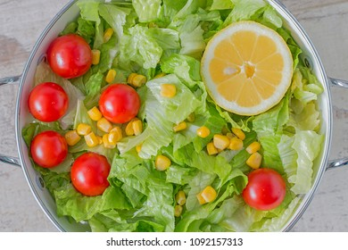 A colander with green salad, cherry tomatoes, corn and lemon. From above.