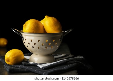 Colander with whole lemons on table against dark background