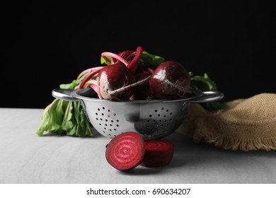 Colander with young beets on table