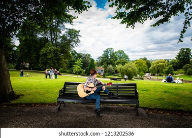 Colchester, Essex - 1st August 2018 - A handsome young man in a hat playing guitar and busking for money