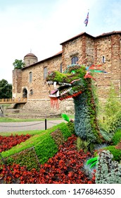 COLCHESTER, ESSEX, UK - AUGUST 4, 2019. A floral dragon display in front of the ancient castle in Colchester, Essex, England, UK. Colchester is a location name in the Game of Thrones TV fantasy.