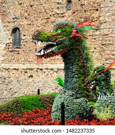 COLCHESTER, ESSEX, UK - AUGUST 4, 2019. A floral dragon display in front of the ancient castle in Colchester, Essex, England, Colchester is a location name in the Game of Thrones TV fantasy.