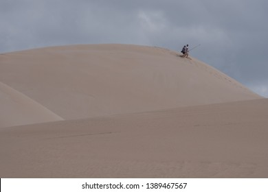 Colchester, South Africa. March 2019. Peoplemaking their way down from the top of the sand dunes, at the Alexandria coastal dune fields near Addo / Colchester on the Sunshine Coast in South Africa.