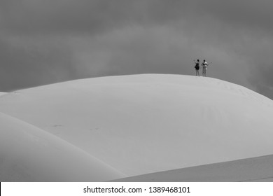 Colchester, South Africa. March 2019. People at the top of the sand dunes, at the Alexandria coastal dunes near Addo / Colchester on the Sunshine Coast in South Africa. Photographed in monochrome.