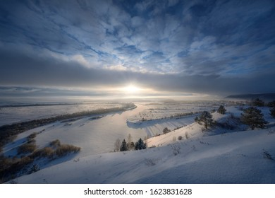 Cold Air Clouds Front.  View of the winter river from the height of the mountain.