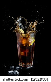 Cold alcohol drink with lime slice and ice cubes. cuba libre splash cocktail on a black background