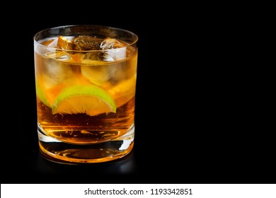 Cold alcohol drink with lime slice and ice cubes. cuba libre cocktail on a black background