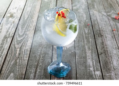 Cold alcoholic gin and tonic cocktail in a glass. Delicious drink made of alcohol and lemon on a table.