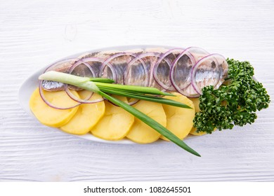 Cold appetizer for a feast, herring, potato and greens on a white wooden background