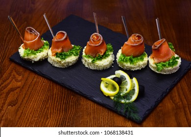 Cold appetizers, canape with red fish, wooden background. Canape with salad leaves, red fish, lemon and dill. Restaurant dish concept. Delicious snacks served in restaurant on black dishes.