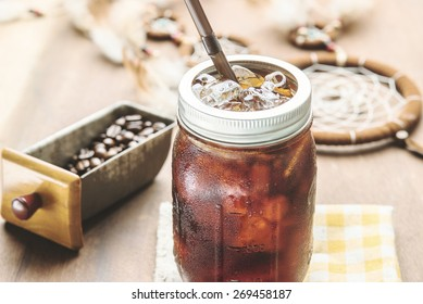 Cold arabica coffee with iced in vintage jar. Photo in vintage color tone style.
