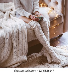 Cold autumn or winter weekend while drinking warm cocoa with marshmellows. Lazy day in knitted socks on the couch. Cosy scene, hygge concept.