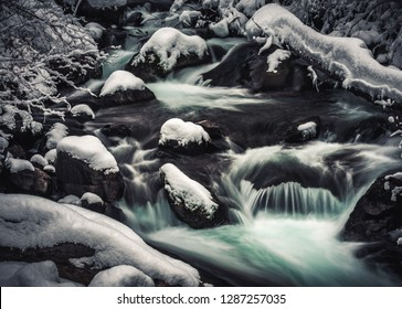 A cold, babbling stream of blue tinted melt water flows after a winter snowstorm in Big Cottonwood Canyon, part of the Wasatch Mountains near Salt Lake City, Utah, USA.