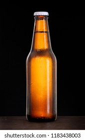 Cold beer bottle with condensation of water drops on black