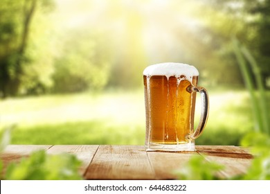 Cold beer in garden on wooden desk of free space for your decoration