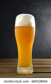 Cold beer in glass on wooden table