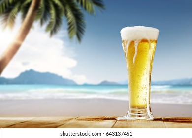 Cold beer on desk and background of summer beach with palm