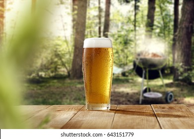 cold beer on desk and grill time in forest