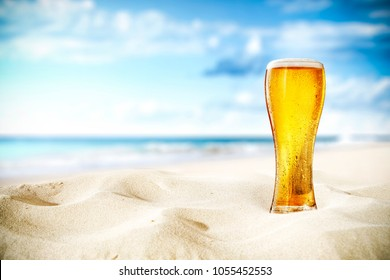 Cold beer on sand and beach background