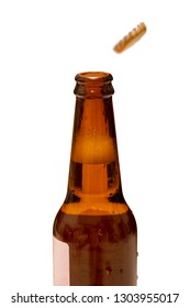 Cold beer opened bottle with popping caps on white background. Soda bottle.