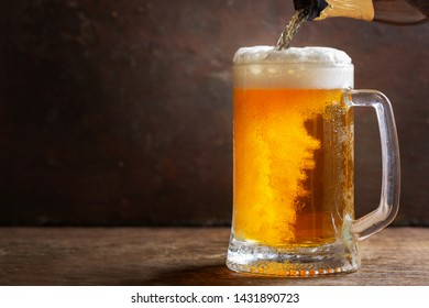 cold beer pouring from bottle into mug