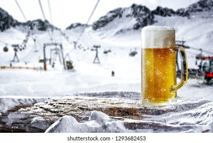 Cold beer and winter time in Alps. Landscape of mountains. Free space for your bottle.