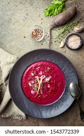 Cold Beetroot mashed soup with cream, apple, cheese and thyme in a dark bowl over stone background, top view.