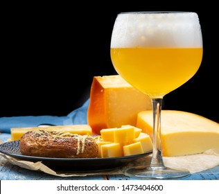 Cold belgian beer in glass served in cafe with variety of hard cheeses, tasty european food close up