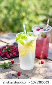 Cold beverage. Refreshing summer drink lemon, refreshing summer drink raspberry with basil and ice on a wooden kitchen table. Copy space.