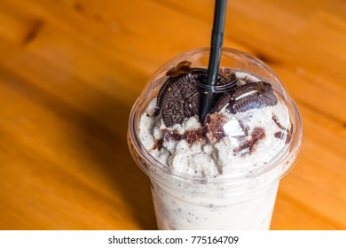 Cold Black biscuit Cookies and Cream milkshake with sweet milk on wooden table with copy space.