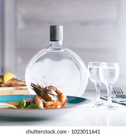 Cold bottle of vodka served with shrimps and two glasses
