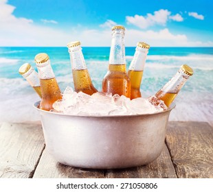 cold bottles of beer in bucket with ice over sea