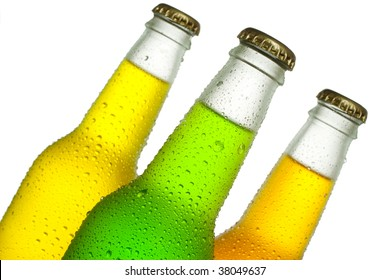 Cold bottles of tropical drinks on white background