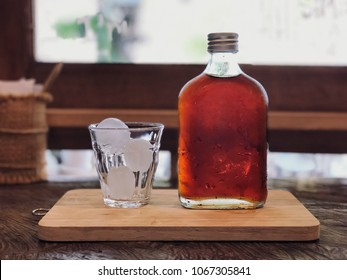 Cold brew coffee bottom and glass on the wooden tray with cafe light. Relaxing with ice coffee.
