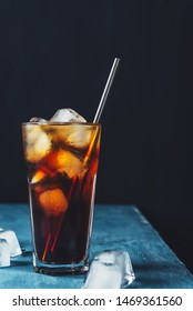 Cold brew coffee in a glass with metal straw on a dark background.Iced coffee with ice cube.