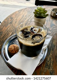 Cold Brew Coffee with Ice at Cafe Shop served with Cookie on Wooden Table.