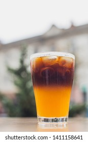 cold brew coffee with orange juice. Glass with cold coffee and ice on the background of  bblurred city street Selective focus