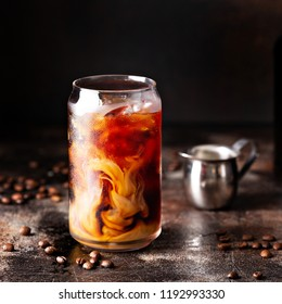 Cold brew iced coffee in a glass with swirls of milk or creamer