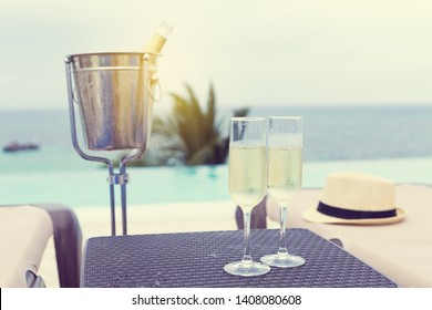 Cold champagne bottle in ice bucket and two glasses of sparkling wine on rattan table near infinity swimming pool