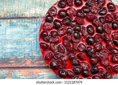 Cold cheesecake with cherry jelly on table