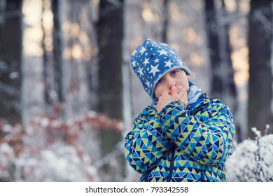 Cold child in winter snow forest warming his hands, soft evening ligh.