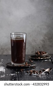 Cold chocolate coffee in the tall glass on the black wooden table