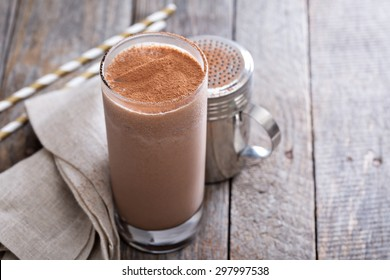 Cold chocolate milkshake in tall glass with ice