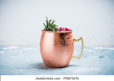 Cold christmas Moscow Mule cocktail in copper mug on the rustic background. Shallow depth of field.